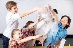 Niños felices positivos que intentan tocar un frasco químico Imagen de archivo libre de regalías