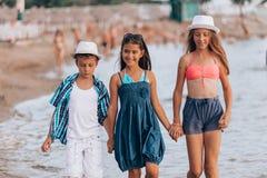 Ni?os felices que caminan junto a trav?s del agua fotografía de archivo libre de regalías