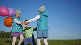 Niños felices que circundan llevando a cabo las manos en el parque con los globos almacen de metraje de vídeo