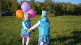 Niños felices que circundan llevando a cabo las manos en el parque con los globos Día de fiesta del ` s de los niños en el aire a almacen de metraje de vídeo