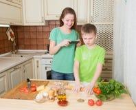 Niños felices que cocinan la cocina hecha en casa de la pizza en casa adolescente Imagenes de archivo