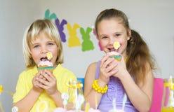 Niños felices que comen las magdalenas en la escena de Pascua Imágenes de archivo libres de regalías