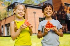 Niños felices que comen una sandía madura Imagen de archivo