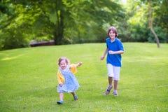 Niños felices que corren en un parque Imágenes de archivo libres de regalías