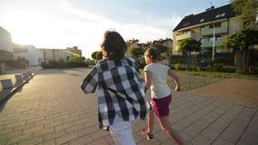 Niños felices que corren juntas llevar a cabo las manos en el camino Los rayos del sol brillan en sus caras metrajes