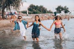 Ni?os felices que corren junto a trav?s del agua y que llevan a cabo las manos en la playa foto de archivo