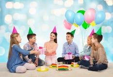 Niños felices que dan presentes en la fiesta de cumpleaños Imagenes de archivo