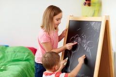 Niños felices que dibujan en el tablero de tiza en casa Imágenes de archivo libres de regalías