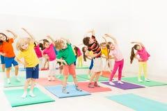 Niños felices que hacen ejercicios de doblez del lado en gimnasio Imagenes de archivo