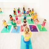 Niños felices que hacen ejercicios del arrodillamiento en gimnasio fotos de archivo
