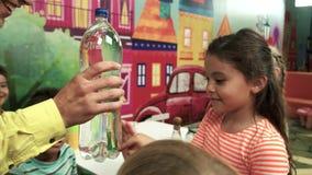 Niños felices que hacen el experimento con la botella de agua almacen de metraje de vídeo