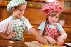 Niños felices que juegan al cocinero en la cocina fotos de archivo