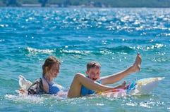 Niños felices que juegan con el colchón en el mar Fotos de archivo libres de regalías