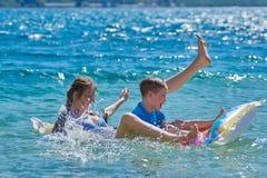 Niños felices que juegan con el colchón en el mar Foto de archivo libre de regalías