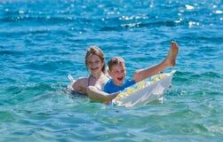 Niños felices que juegan con el colchón en el mar Imagenes de archivo