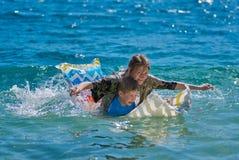 Niños felices que juegan con el colchón en el mar Fotografía de archivo