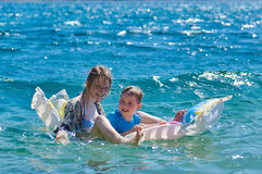 Niños felices que juegan con el colchón en el mar Fotos de archivo