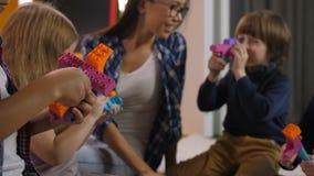 Niños felices que juegan con los bloques coloridos del juguete metrajes