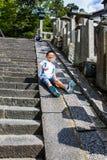 Niños felices que juegan deslizarse del borde de un stairca de piedra Foto de archivo libre de regalías