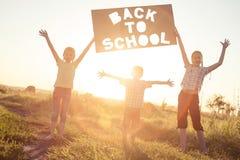 Niños felices que juegan en el campo en el tiempo de la puesta del sol Foto de archivo libre de regalías