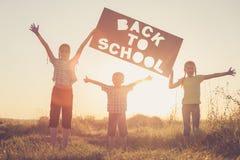Niños felices que juegan en el campo en el tiempo de la puesta del sol Fotos de archivo