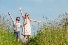 Niños felices que juegan en el campo en el tiempo del día Fotos de archivo libres de regalías