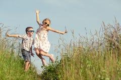 Niños felices que juegan en el campo en el tiempo del día Imágenes de archivo libres de regalías