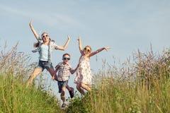 Niños felices que juegan en el campo en el tiempo del día Imagen de archivo