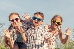 Niños felices que juegan en el campo en el tiempo del día Fotos de archivo