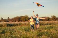 Niños felices que juegan en el campo en el tiempo del día Imagenes de archivo