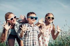 Niños felices que juegan en el campo en el tiempo del día Imagen de archivo libre de regalías