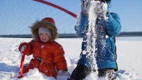 Niños felices que juegan en el parque en un día de invierno soleado Paisaje del invierno Nevado outdoors almacen de metraje de vídeo