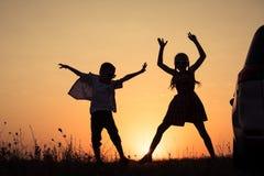 Niños felices que juegan en el parque en el tiempo de la puesta del sol Imagen de archivo libre de regalías