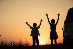 Niños felices que juegan en el parque en el tiempo de la puesta del sol Foto de archivo libre de regalías