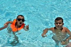Ni?os felices que juegan en la piscina foto de archivo