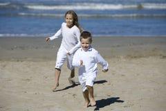 Niños felices que juegan en la playa Foto de archivo libre de regalías