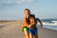 Niños felices que juegan en la playa Imagenes de archivo