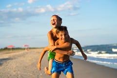 Niños felices que juegan en la playa Imagen de archivo libre de regalías