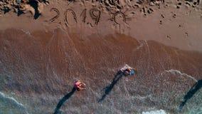 Niños felices que juegan en la playa Año Nuevo 2019 escrito en la arena