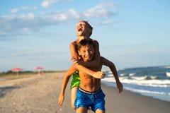 Niños felices que juegan en la playa el días de fiesta Fotografía de archivo