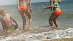 Niños felices que juegan en la playa en el tiempo de la puesta del sol Concepto de familia amistosa feliz metrajes