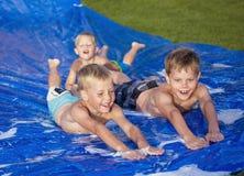 Niños felices que juegan en un resbalón y una diapositiva al aire libre Imagenes de archivo
