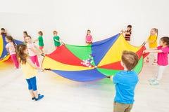 Niños felices que juegan a juegos del paracaídas en gimnasio Imagen de archivo libre de regalías