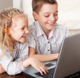 Niños felices que juegan la computadora portátil Imágenes de archivo libres de regalías