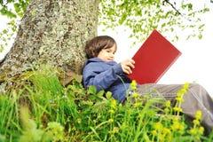 Niños felices que leen el libro Imagen de archivo