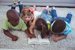 Niños felices que leen un libro junto fotos de archivo