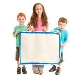 Niños felices que llevan a cabo la muestra en blanco Imagen de archivo libre de regalías