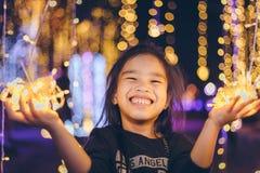 Niños felices que llevan a cabo una luz en un ` s Eve del Año Nuevo Noche de la calle Fotos de archivo libres de regalías