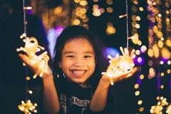 Niños felices que llevan a cabo una luz en un ` s Eve del Año Nuevo Noche de la calle Fotos de archivo