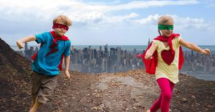 Niños felices que llevan el cabo rojo y la máscara que se divierten contra paisaje urbano Fotos de archivo libres de regalías